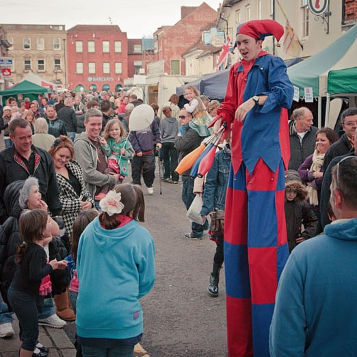 Stilt-walking jester at festival web sqr